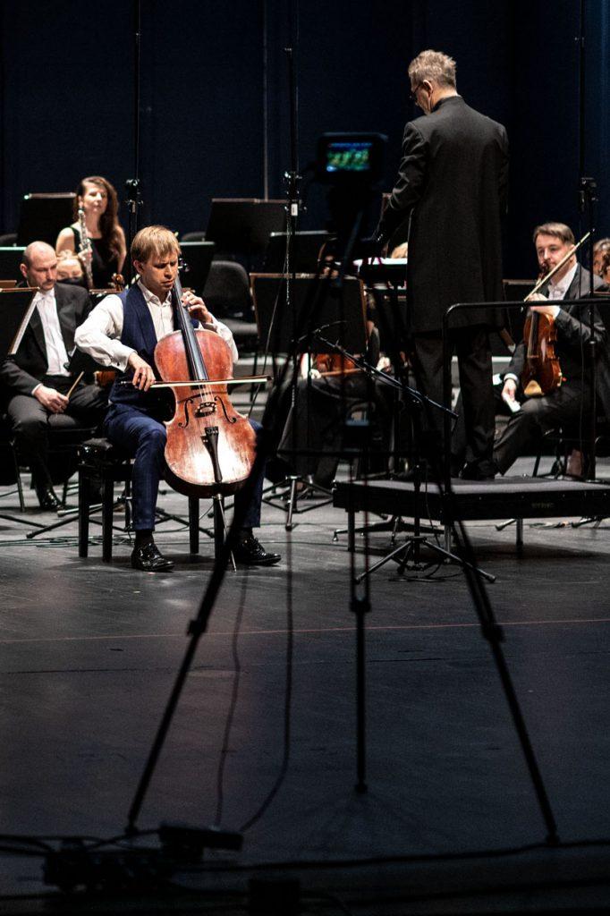 Na środku siedzi mężczyzna grający na wiolonczeli. Dookoła niego siedzą muzycy z sekcji dętej orkiestry. Przed nimi stoi dyrygent. Z przodu statyw z aparatem.