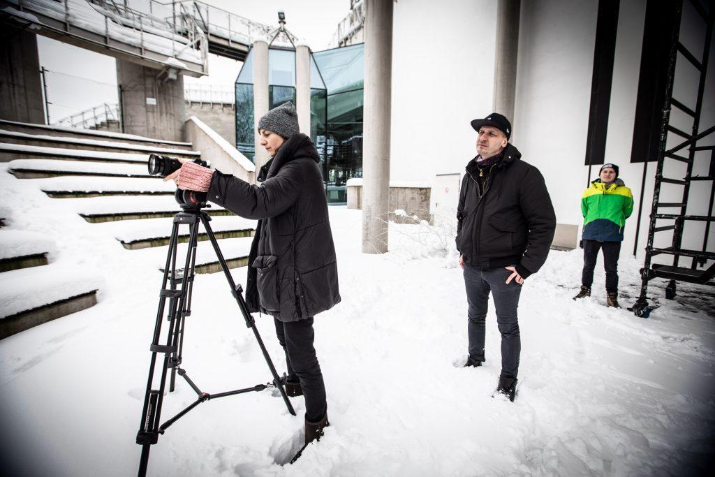 Scena Amfiteatru przykryta śniegiem. Po lewej stronie stoi kobieta w zimowej kurtce przed statywem z aparatem. Za nią stoi dwóch mężczyzn.