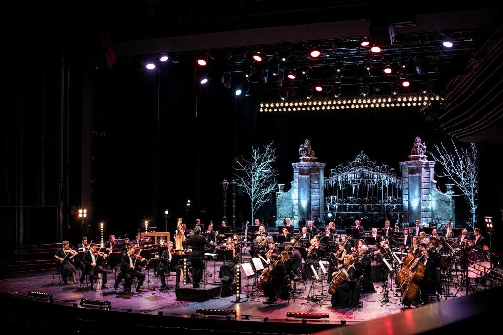 Koncert na Nowy Rok. Na scenie siedzi Orkiestra Opery i Filharmonii Podlaskiej. Z przodu stoi dyrygent. Na końcu podświetlona, ozdobna brama. Po obydwu jej stronach drzewa bez liści podświetlone białym światłem.