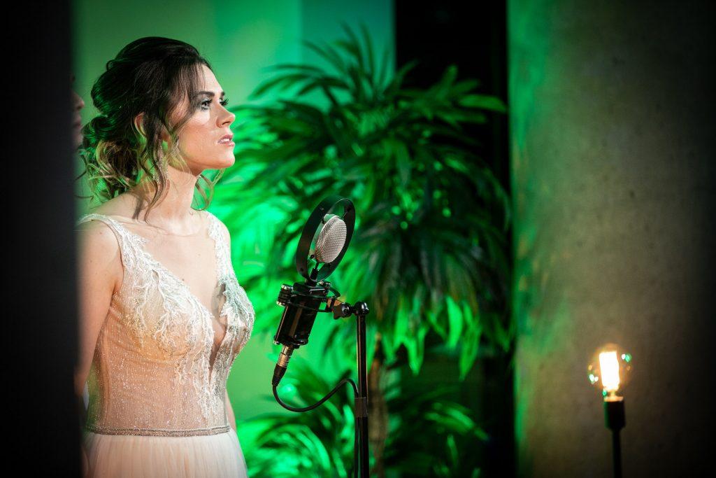 Zbliżenie na kobietę w białej, długiej sukni stoi przy mikrofonie. Za nią oświetlone na zielono drzewo.