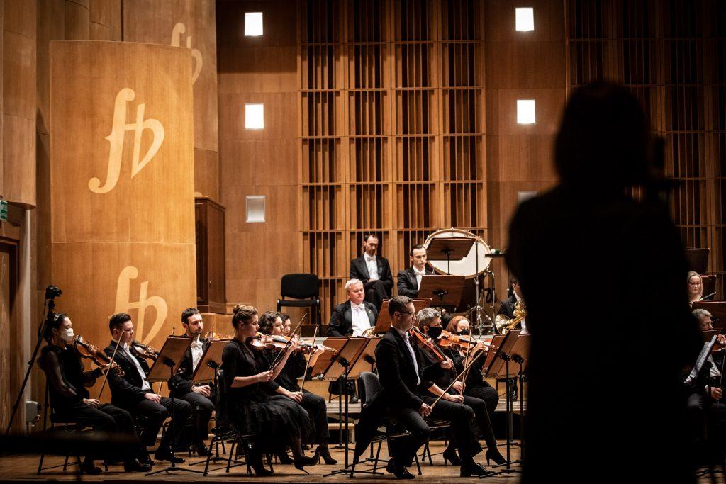 Scena sali koncertowej. Na środku, przy pulpitach siedzi część grupy smyczkowej. Dalej widoczna część sekcji dętej. Po prawej stronie stoi tyłem kobieta.