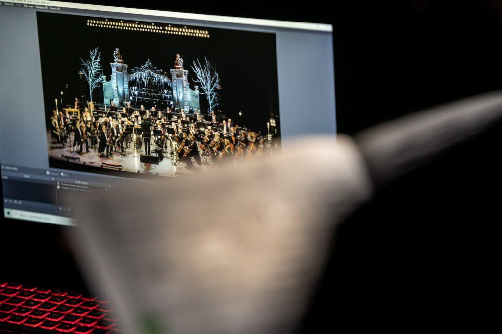 Na zdjęciu zbliżenie na monitor z klawiaturą. Na monitorze wyświetla się scena.Na niej trwa koncert. Na środku na podeście stoi dyrygent. Dookoła siedzi Orkiestra Opery i Filharmonii Podlaskiej.