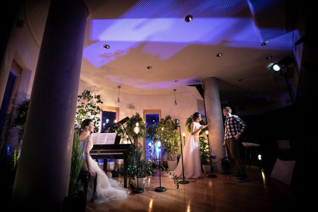 Dwie kobiety w białych sukniach, jedna siedzi przy pianinie, druga rozmawia z mężczyzną w koszuli w kratę. Wokół nich kwiaty w donicach i lampy na wysokich, czarnych podstawach.