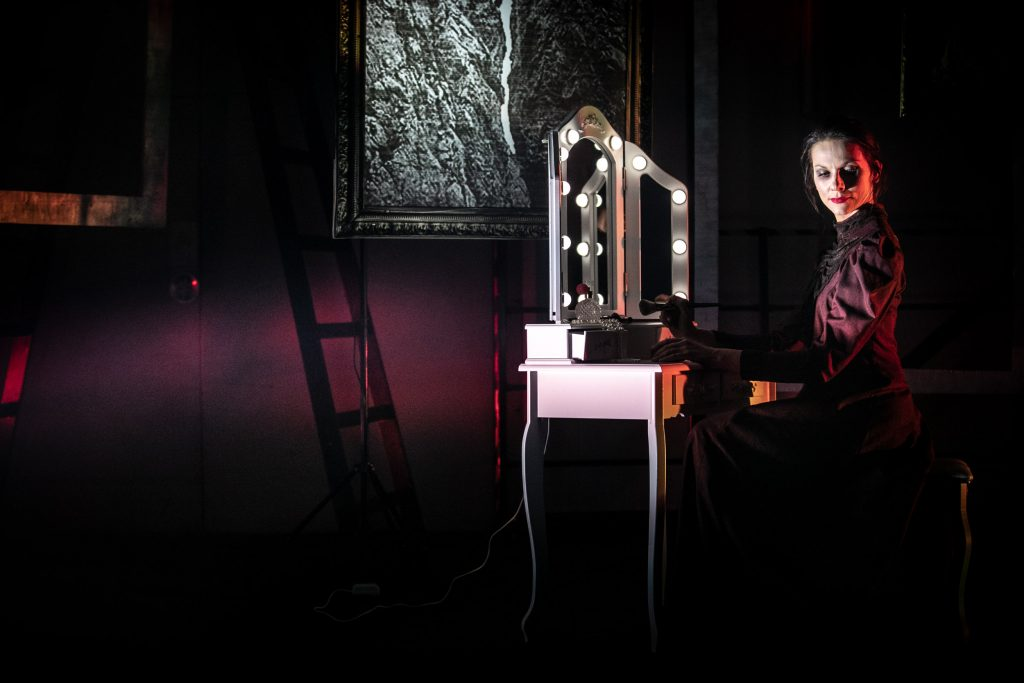 Na środku stoi biała toaletka z podświetlonym lustrem. Przed nią siedzi kobieta z głową odwróconą na bok. Za toaletką przy ścianie wisi obraz.