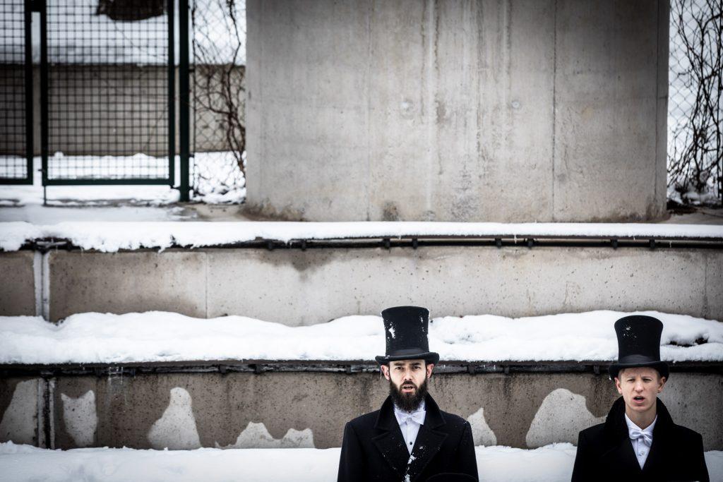 Zbliżenie na dwóch mężczyzn w czarnych cylindrach. Za nimi kilka zaśnieżonych rzędów Amfiteatru