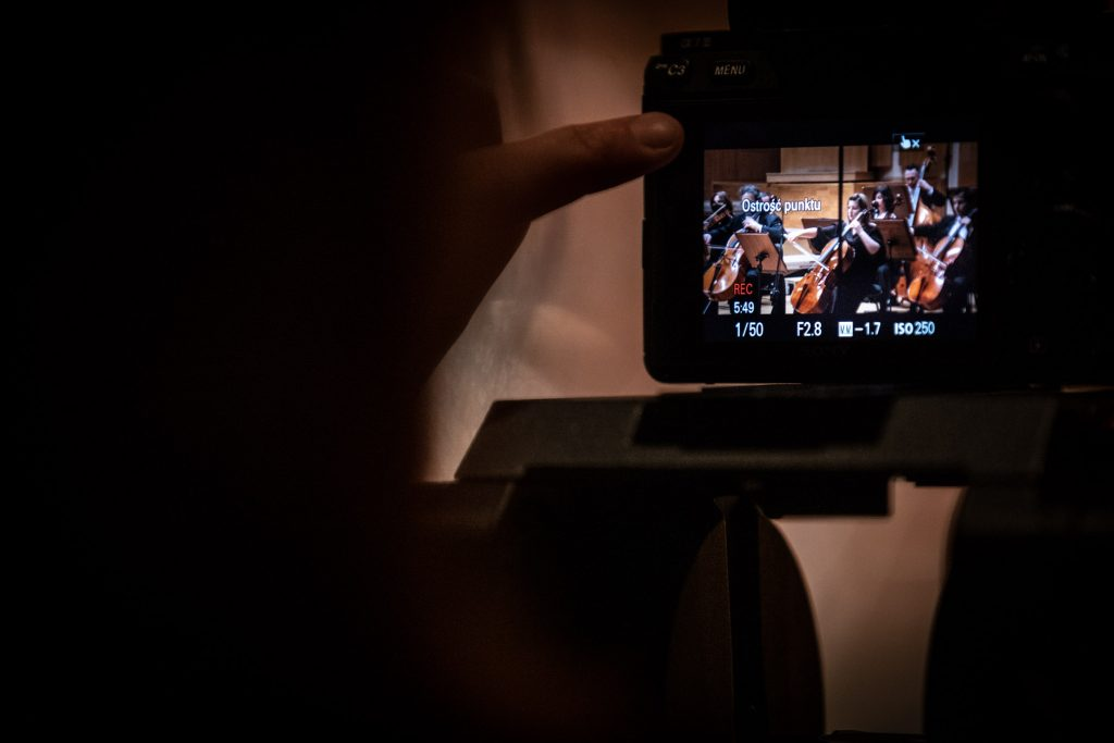 Na zdjęciu w prawym rogu widoczny monitor. Na nim wyświetla się kadr z koncertu.