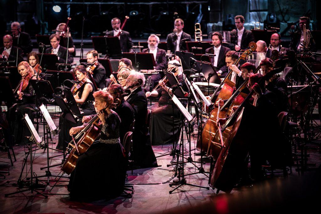 Zdjęcie orkiestry zrobione z boku. Część sekcji smyczkowej i część sekcji dętej gra na swoich instrumentach.