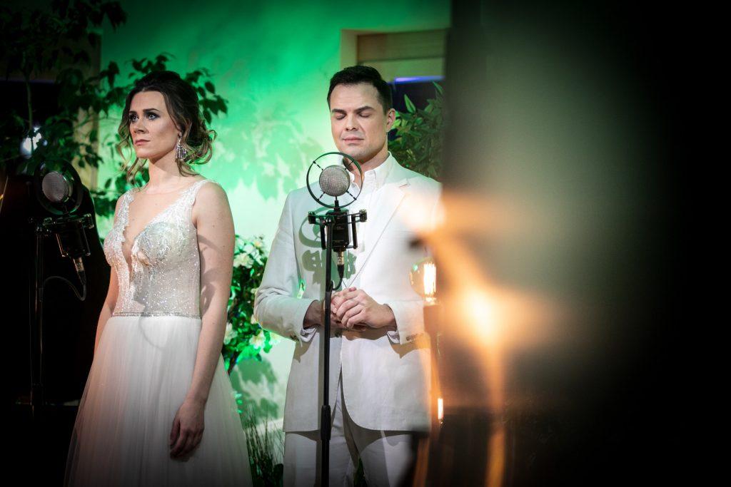 Kobieta i mężczyzna ubrani na biało stoją przy mikrofonach. Za nimi widać podświetlone na zielono drzewa.
