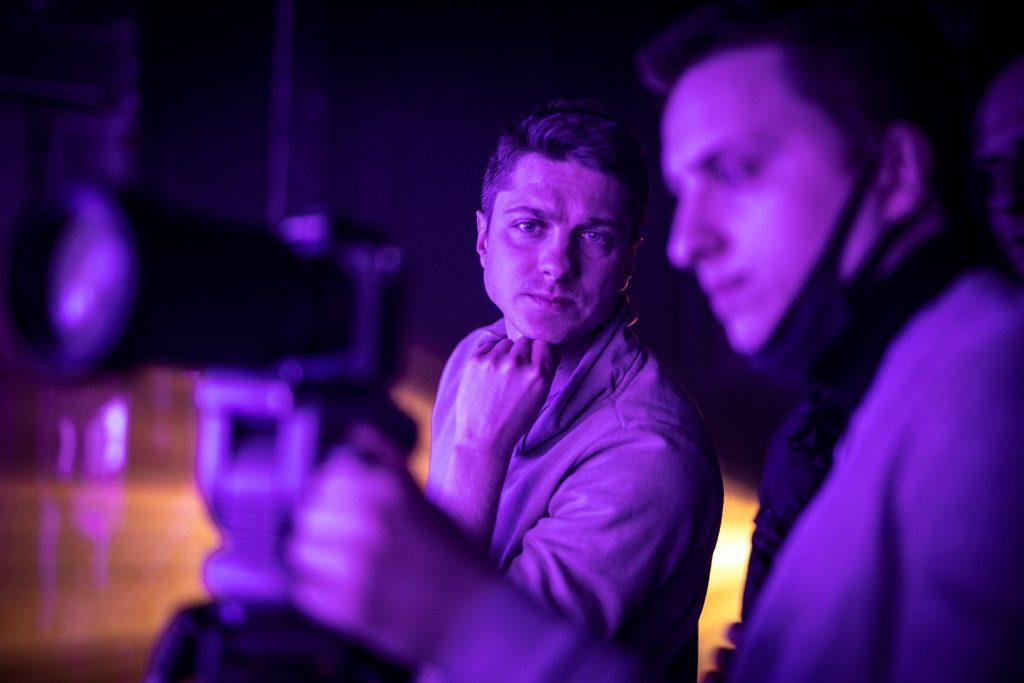 Dwóch mężczyzn siedzących obok siebie patrzy na aparat stojący przed nimi.