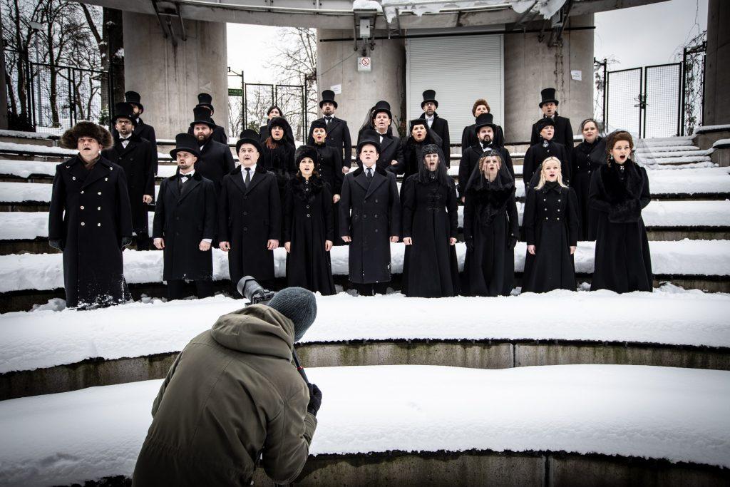 Widownia amfiteatru opery zimą .Kilkanaście osób ubranych na czarno stoi w śniegu pomiędzy rzędami. Przed nimi mężczyzna z aparatem.