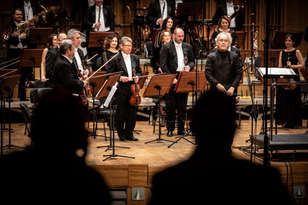 Zbliżenie na scenę sali koncertowej. Po prawej stronie stoi dyrygent. Dookoła przy pulpitach stoi Zespół Kameralny Ars Iuvenum z Opery i Filharmonii Podlaskiej.
