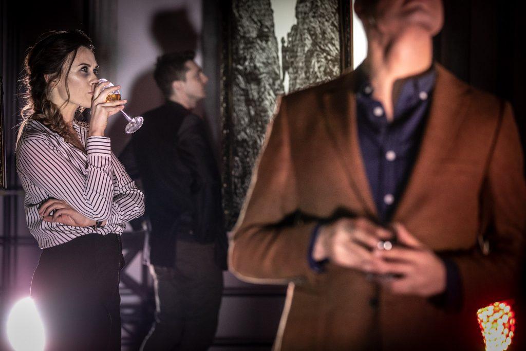 Po lewej stronie stoi kobieta z kieliszkiem przy ustach. Po prawej stronie widoczna sylwetka mężczyzny. W oddali widać mężczyznę stojącego bokiem.