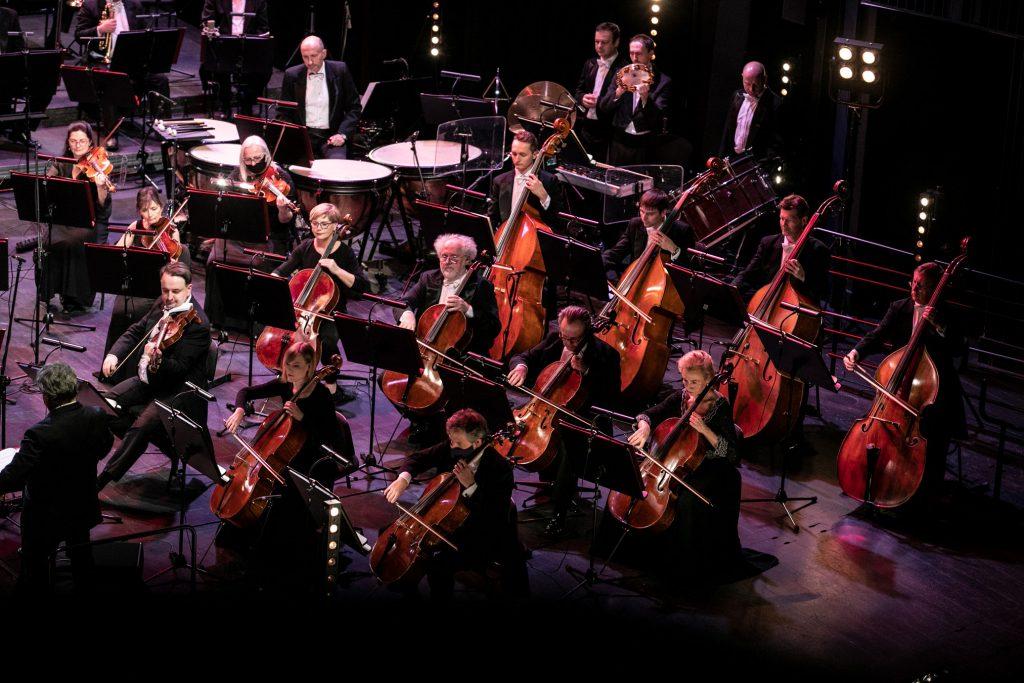 Zbliżenie na część orkiestry. Z przodu siedzi część sekcji smyczkowej, za nimi siedzą artyści sekcji instrumentów perkusyjnych.