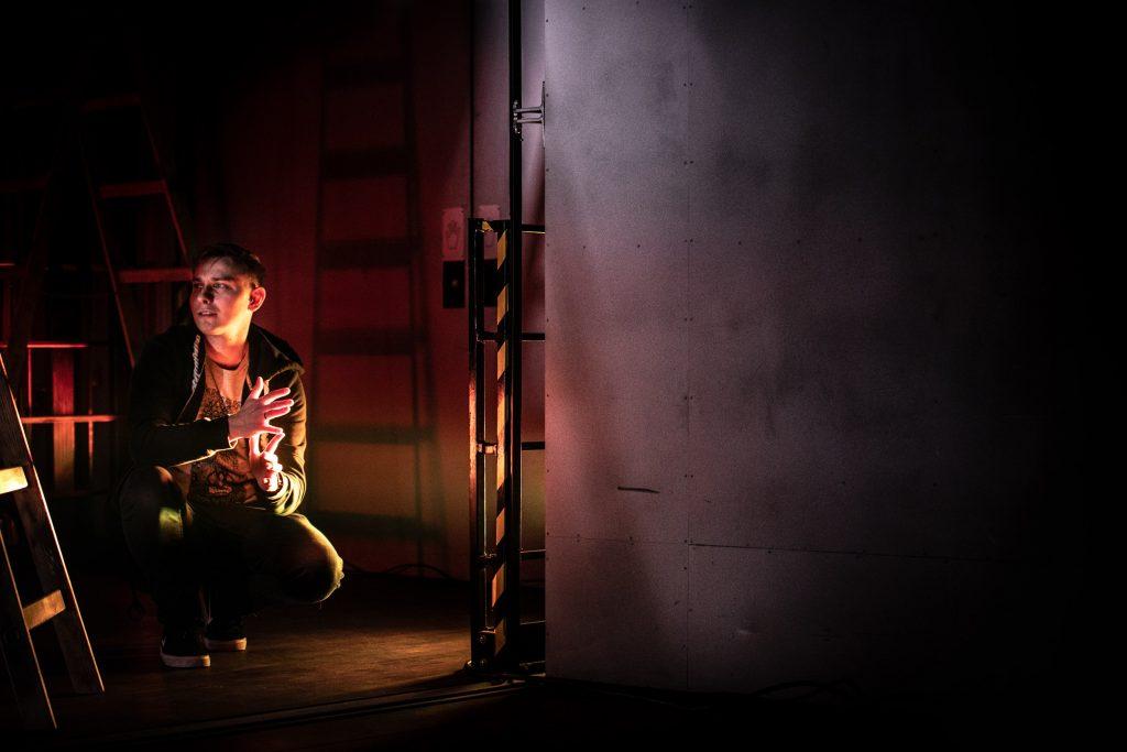 Winda towarowa Opery w półmroku. Po lewej stronie mężczyzna siedzi na zgiętych nogach. Za nim rozstawione dwie drabiny.