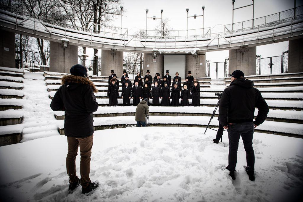 Widownia amfiteatru opery zimą .Kilkanaście osób ubranych na czarno stoi w śniegu pomiędzy rzędami. Przed nimi mężczyzna z aparatem. Z przodu dwóch mężczyzn stoi tyłem na scenie.
