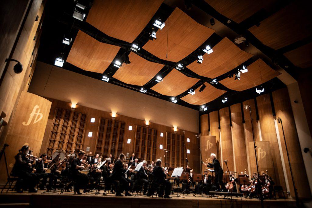 Scena sali koncertowej przy ulicy Podleśnej. Zdjęcie zrobione z końca widowni. Na scenie siedzi Zespół Kameralny Ars Iuvenum. Przed nimi na podeście stoi dyrygent.