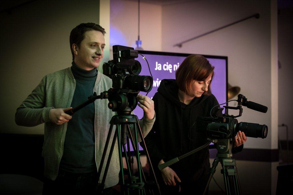 Kobieta i mężczyzna stoją obok siebie. Przed nimi statywy z aparatami. Za nimi duży telewizor.