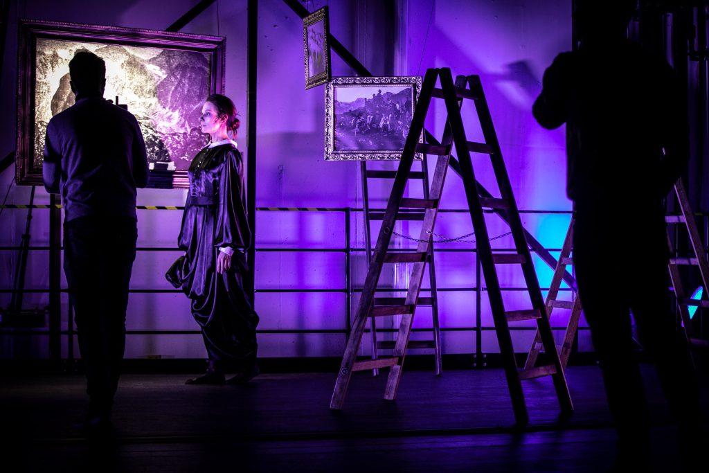 Nagranie koncertu w windzie towarowej. Pomieszczenie oświetlone niebieskim światłem. Na środku stoi rozstawiona drabina. Po jej lewej stronie stoi bokiem kobieta w długiej sukni. Patrzy przed siebie. Obok niej stoi tyłem mężczyzna. Po prawej stronie widoczna czarna sylwetka mężczyzny.