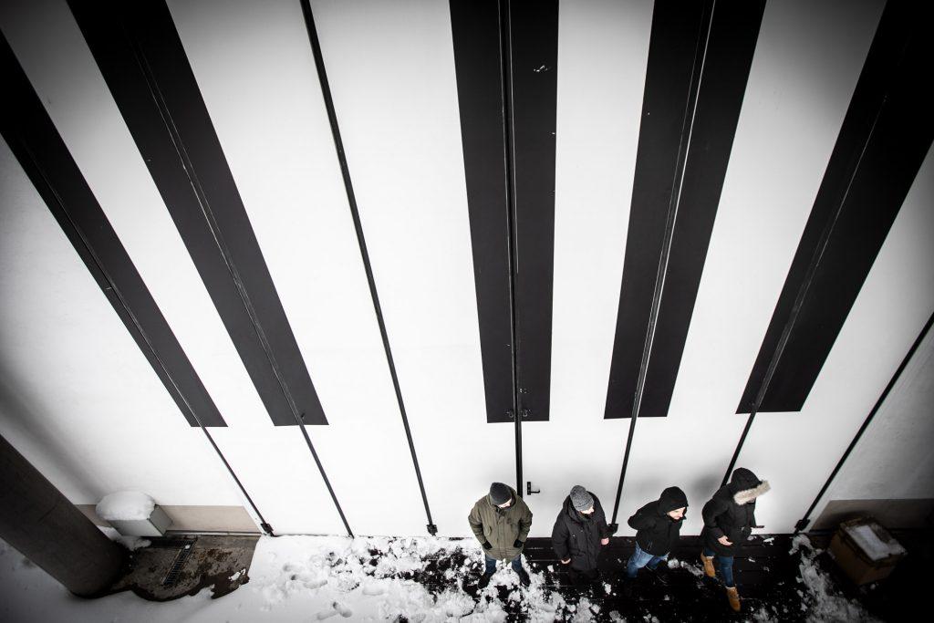 Ściana Amfiteatru przedstawiająca klawisze. Pod nią stoi kilka osób ubranych w zimowe ubrania.