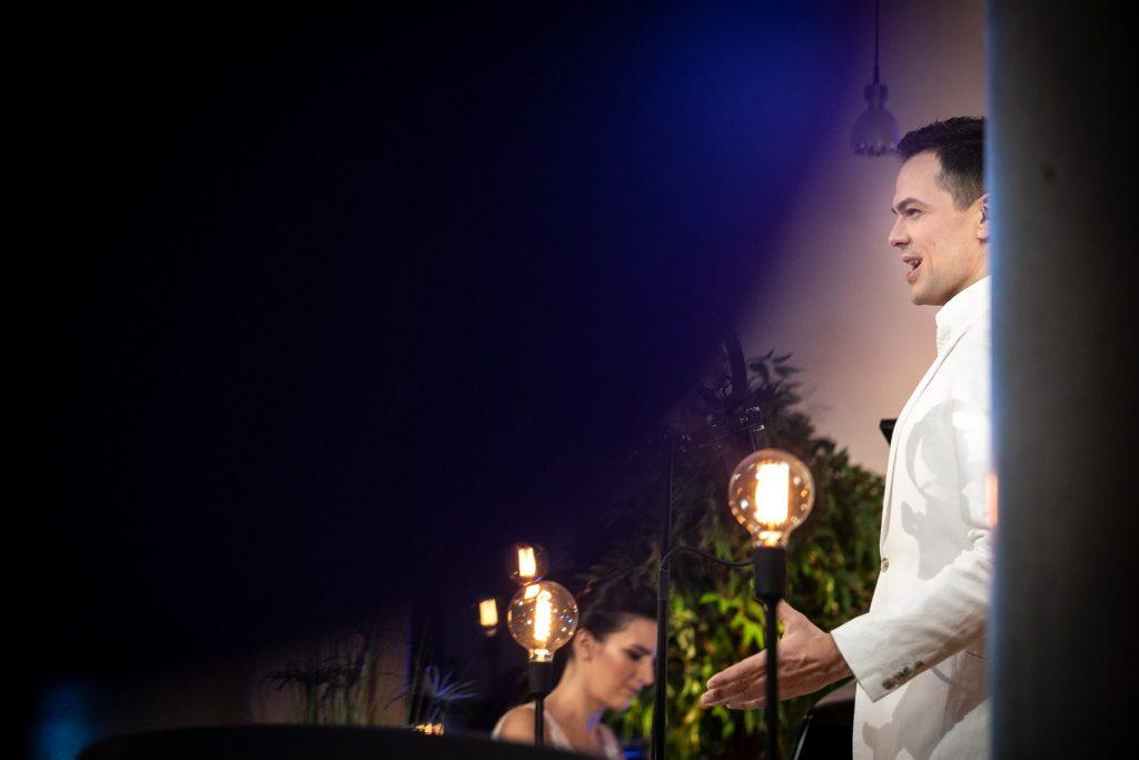 Po prawej stronie stoi mężczyzna w białym garniturze z rękami rozłożonymi na boki. W oddali widać siedzącą kobietę. Za nią stoją rośliny. Przed nimi stoją lampy na wysokich, czarnych podstawkach.