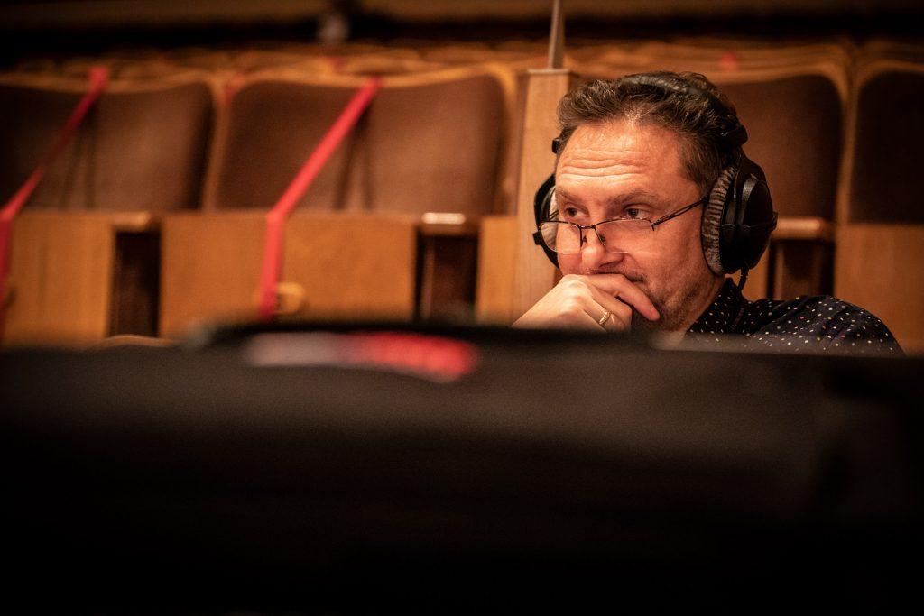 Na widowni sali koncertowej siedzi mężczyzna w słuchawkach.