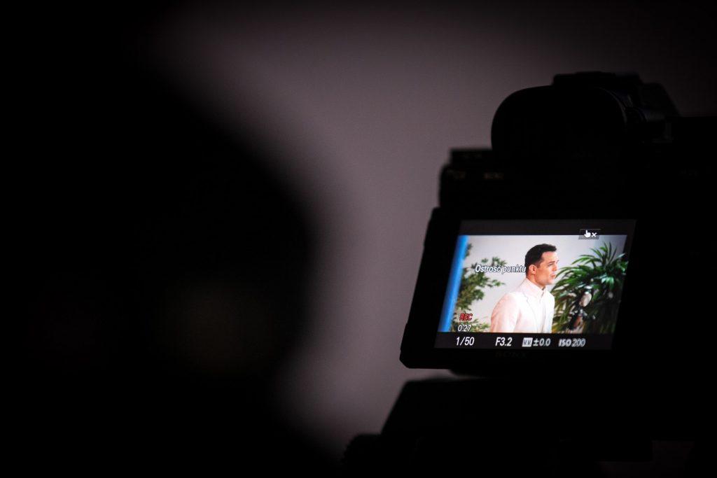 Na zdjęciu widać monitor aparatu, na którym wyświetla się mężczyzna w białym garniturze.