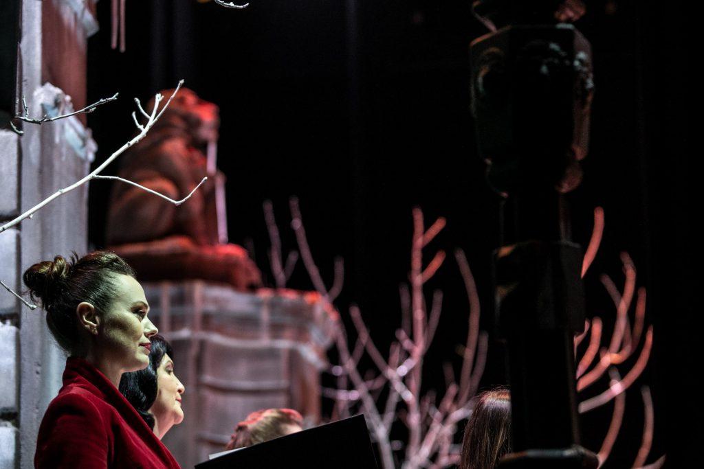 Zdjęcie zrobione z boku. Zbliżenie na chór. Na zdjęciu widać dwie chórzystki, patrzące przed siebie.