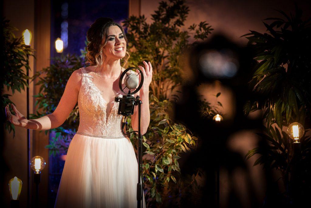 Kobieta w długiej , białej sukni stoi przy mikrofonie na statywie. Za nią podświetlone rośliny. Dookoła lampy na czarnych podstawach.