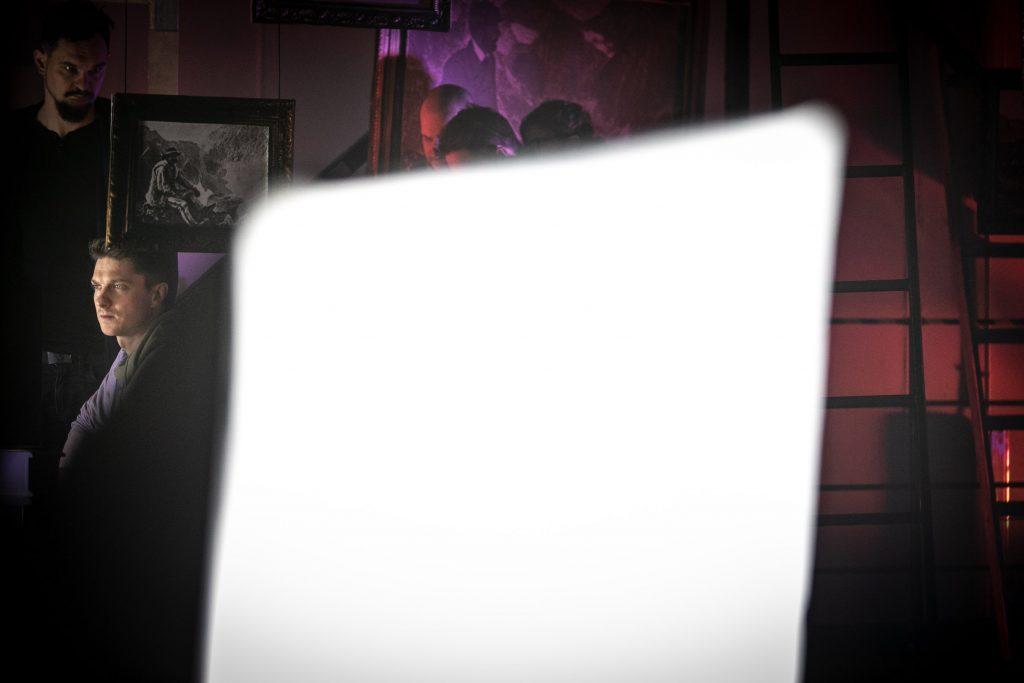 Na środku kadru biała, prostokątna ''plama''. Za nią widocznych kilku mężczyzn. Pomiędzy nimi wiszą na linkach obrazy.