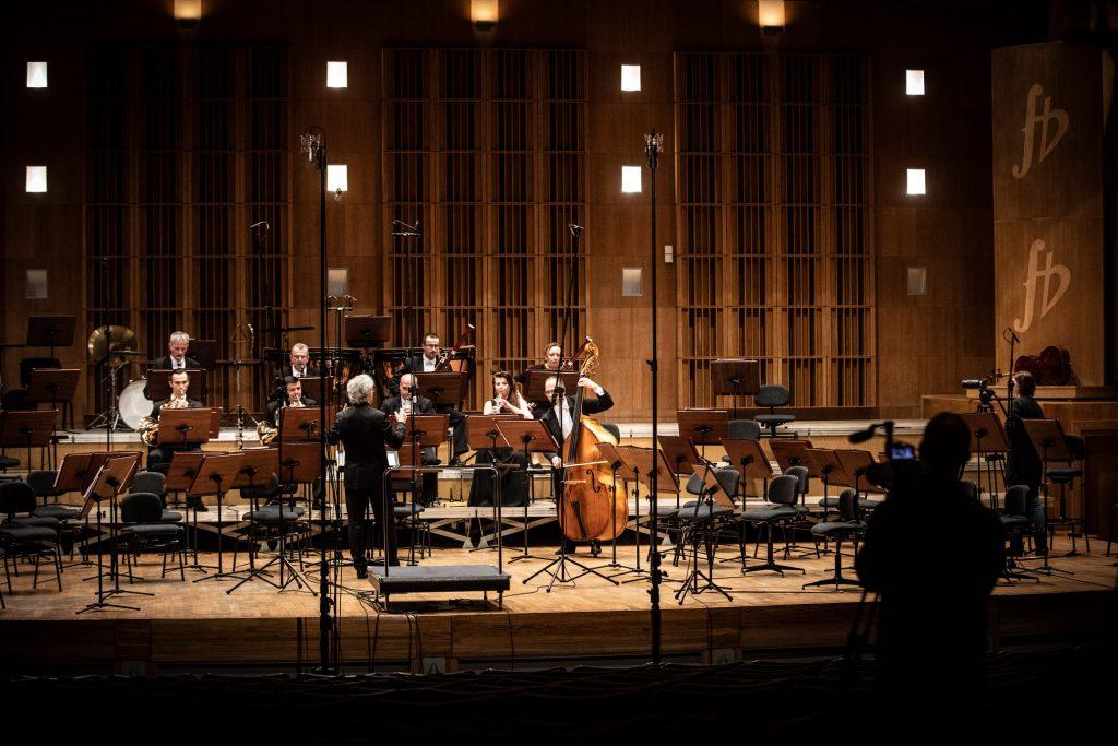 Scena sali koncertowej. Na środku gra kilku muzyków Zespołu Kameralnego. Przed nimi, z uniesionymi rękoma stoi dyrygent. Po obydwu stronach przy pulpitach stoją puste krzesła. Po prawej stronie na widowni stoi mężczyzna z aparatem.