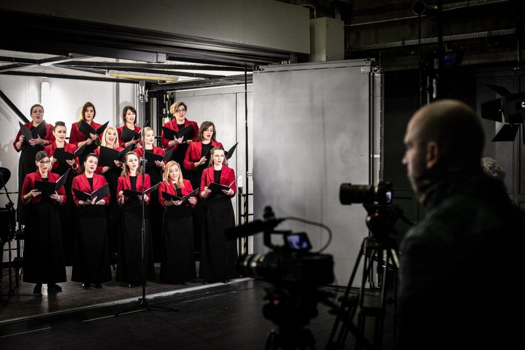 Otwarta winda towarowa w której trwa nagranie. W trzech rzędach stoi część chóru żeńskiego w czarnych sukniach i czerwonych żakietach. Każdy trzyma otwarte teczki. Z przodu po prawej stronie stoi mężczyzna. Przed nim na statywach umieszczone są aparaty.