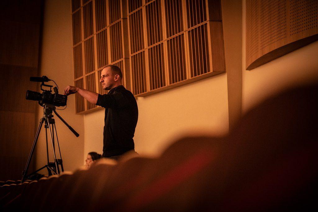 Koniec widowni na sali koncertowej. Przed kamerą na statywie stoi mężczyzna.