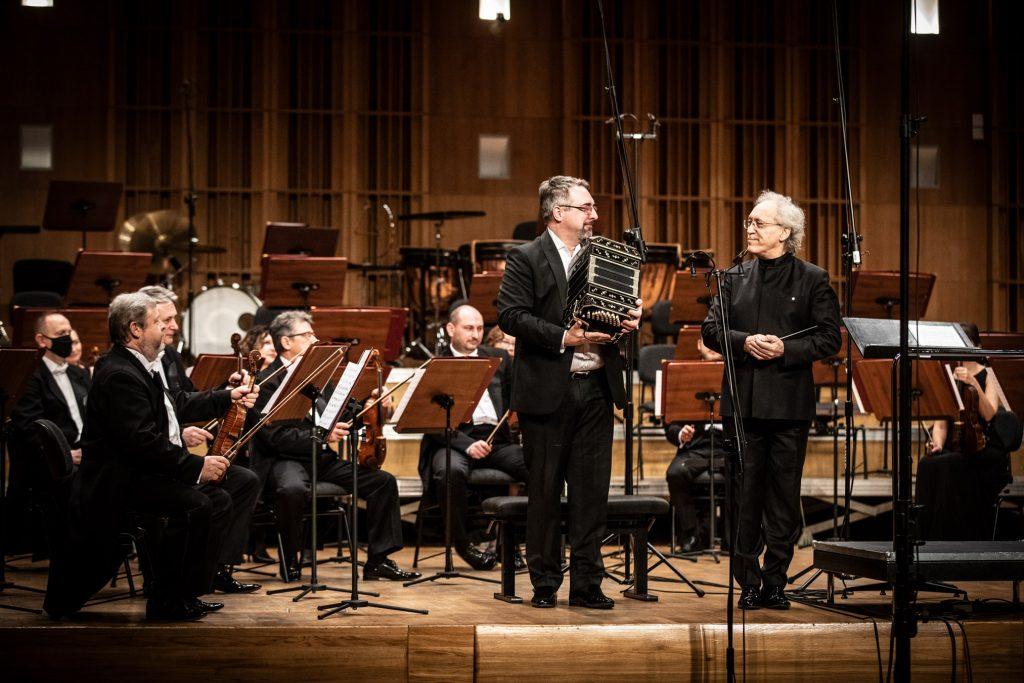 Z przodu na scenie stoi dwóch mężczyzna patrzących w swoim kierunku. Jeden trzyma bandoneon, drugi - batutę. Za nimi siedzi kilku muzyków z grupy smyczkowej.