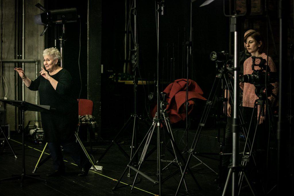 Na zdjęciu kilka statywów stojących blisko siebie. Przed nimi kierownik chóru - Prof. Violetta Bielecka stojąca przed pulpitem do nut. Z rękami uniesionymi do góry. Za nią, za statywem z aparatem stoi kobieta i mężczyzna.