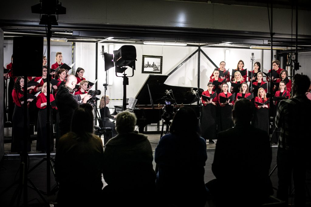 Nagranie koncertu w windzie towarowej. Na środku stoi fortepian, przy nim siedzi kobieta w długiej sukni. Po obydwu stronach stoi w trzech rzędach chór żeński. Wszystkie panie ubrane w czarne, długie suknie i czerwone żakiety, Każda trzyma otwarte teczki. Z przodu, w półmroku, siedzi tyłem kilka osób.