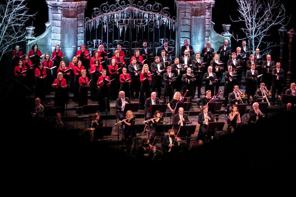 Zbliżenie na scenę podczas koncertu. Z przodu widoczna część sekcji smyczkowej i dętej. Za nimi stoi chór opery. Po lewej stronie żeńska część chóru w czarnych sukniach i czerwonych żakietach. Po prawej stronie męska część chóru we frakach. Wszyscy trzymają otwarte nuty. Za nimi z tyłu widoczna ozdobna brama podświetlona białym światłem.