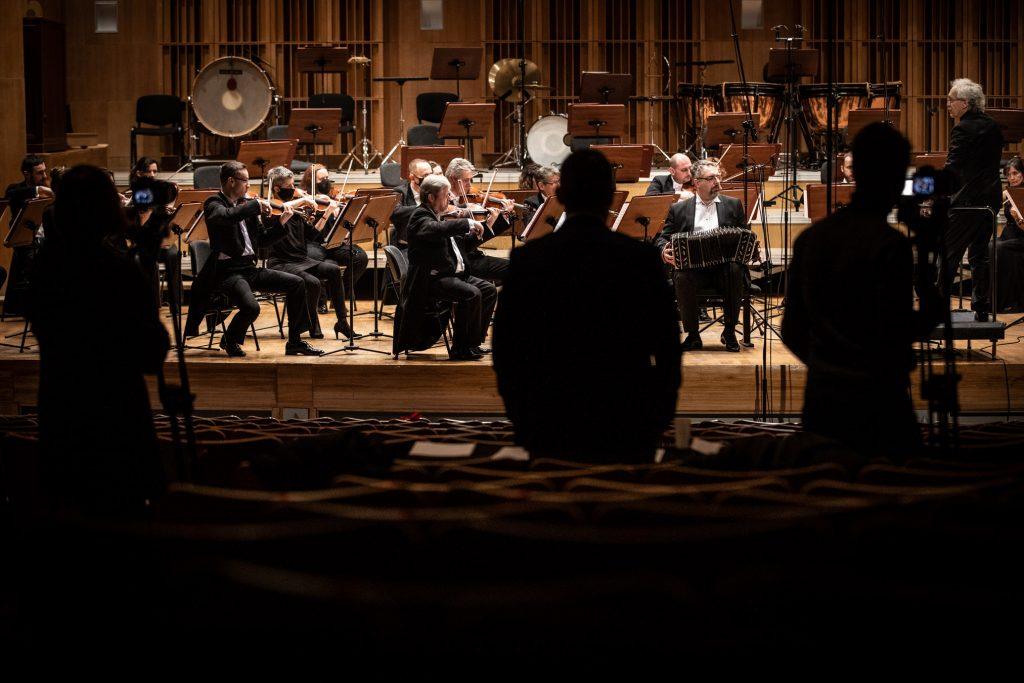 Na scenie gra Zespół Kameralny Ars Iuvenum. Po prawej stronie na podeście stoi dyrygent. Na widowni, tyłem stoi kilka osób.