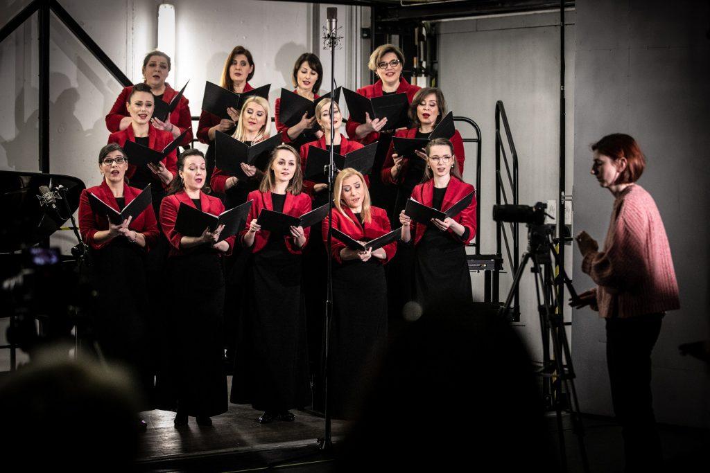 Otwarta winda towarowa w której trwa nagranie. W trzech rzędach stoi część chóru żeńskiego w czarnych sukniach i czerwonych żakietach. Każda z pań trzyma otwarte teczki. Przed nimi widoczny mikrofon na wysokim statywie. Po prawej stronie, za aparatem na statywie, stoi kobieta.