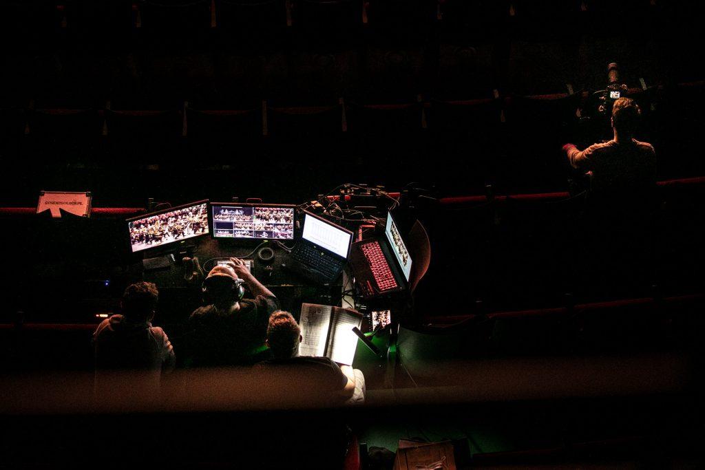 Widownia w półmroku. Zdjęcie zrobione z góry na konsolę akustyków. Trzech mężczyzn siedzi przed kilkoma monitorami. Na nich wyświetla się koncert odbywający się na scenie.