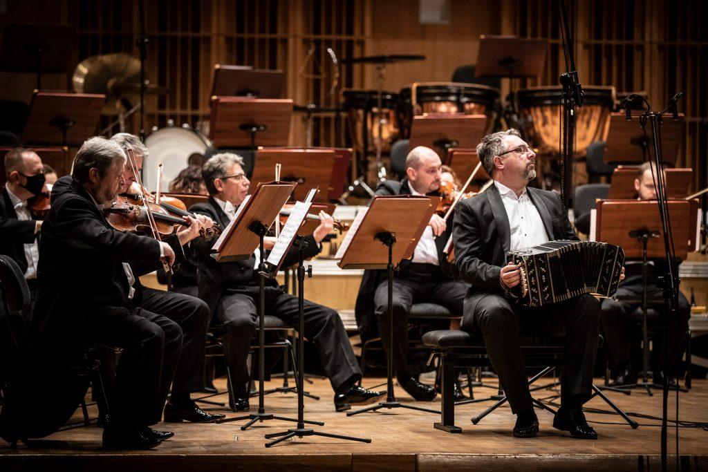 Na scenie sali koncertowej trwa nagranie koncertu. Na zdjęciu widoczna część sekcji smyczkowej. Po prawej stronie siedzi mężczyzna grający na bandoneonie.