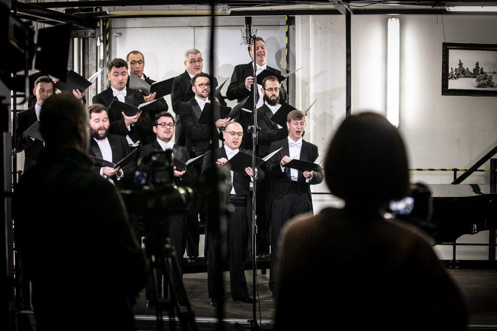 Część chóru męskiego ubranych w czarne fraki stoi w trzech rzędach. Wszyscy trzymają otwarte czarne teczki. Przed nimi widoczny mikrofon na wysokim statywie. Z przodu widać tyłem dwie postacie.