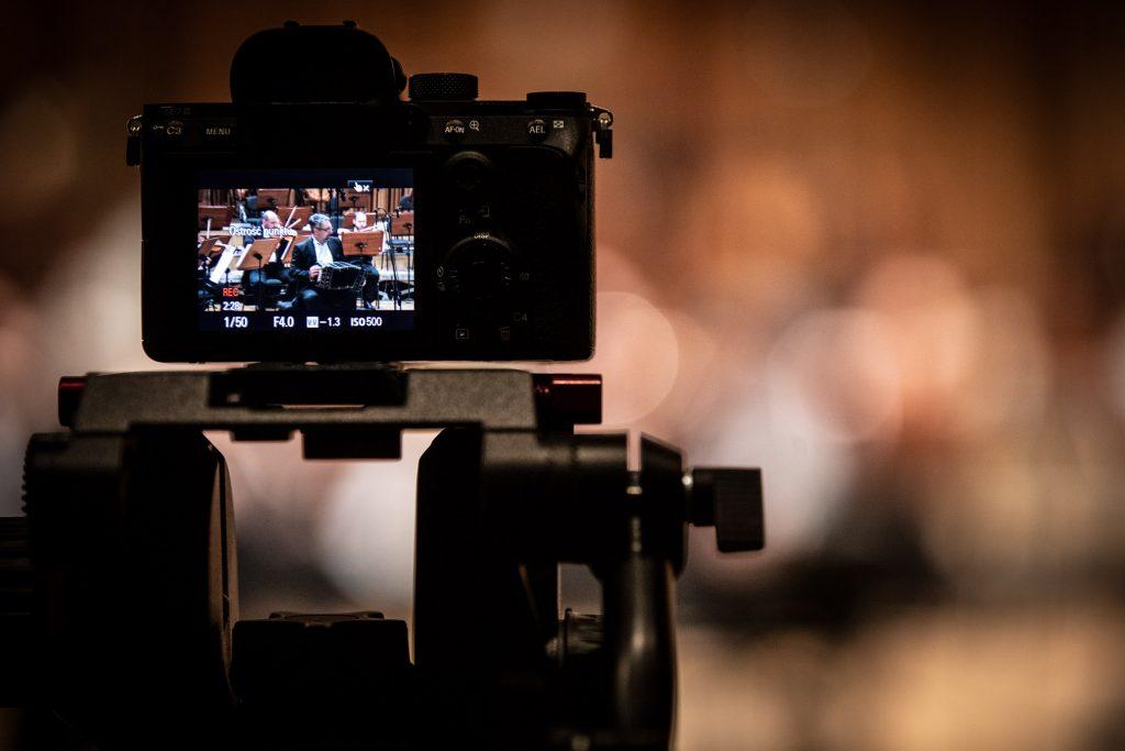 Na zdjęciu widoczny monitor aparatu. Na nim wyświetla się część orkiestry podczas koncertu.