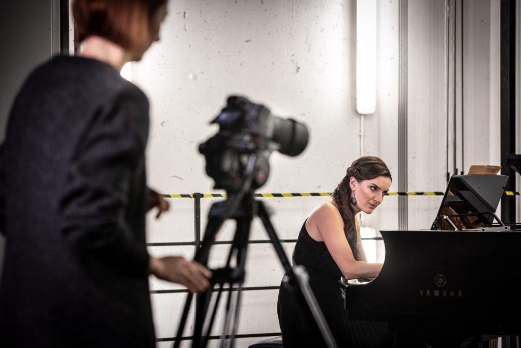Kobieta w czarnej sukni siedzi przy fortepianie. Za nią betonowa ściana z czarną barierką. Z przodu widać aparat na statywie, obok niego stoi kobieta.
