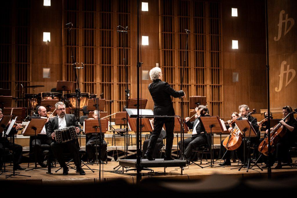 Na środku sceny na podeście stoi dyrygent. Przed nim siedzi grupa smyczkowa Zespołu Kameralnego. Po lewej stronie mężczyzna gra na bandoneonie.