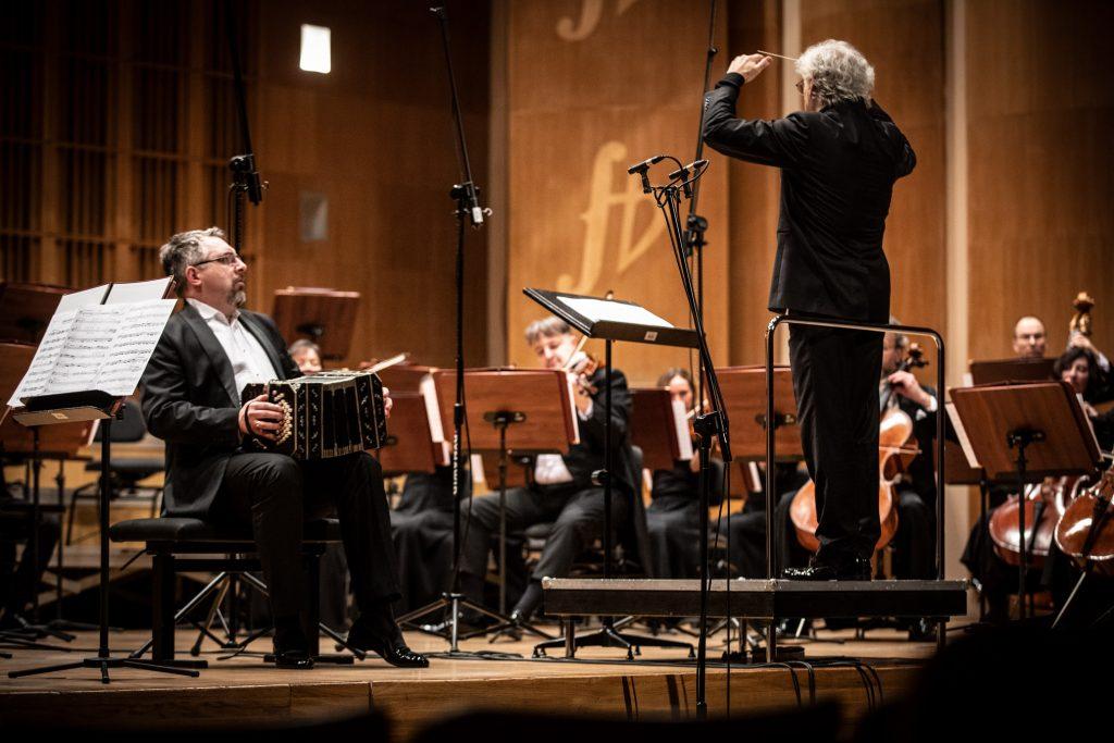 Na podeście po prawej stronie kadru stoi dyrygent. Przed nim siedzi grupa smyczkowa. Po lewej stronie mężczyzna gra na bandoneonie.