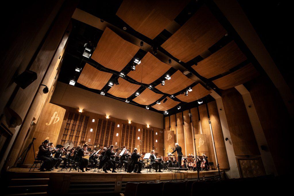 Zdjęcie sceny z boku widowni. Na scenie Zespół Kameralny Ars Iuvenum z Orkiestry Opery i Filharmonii Podlaskiej podczas koncertu. Przed nimi stoi dyrygent.