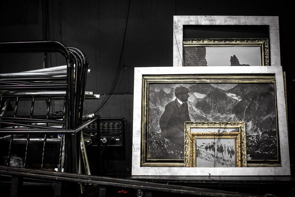 Po prawej stronie, na czarnym tle stoi kilka obrazów. Po lewej stronie - złożone obok siebie czarne barierki.