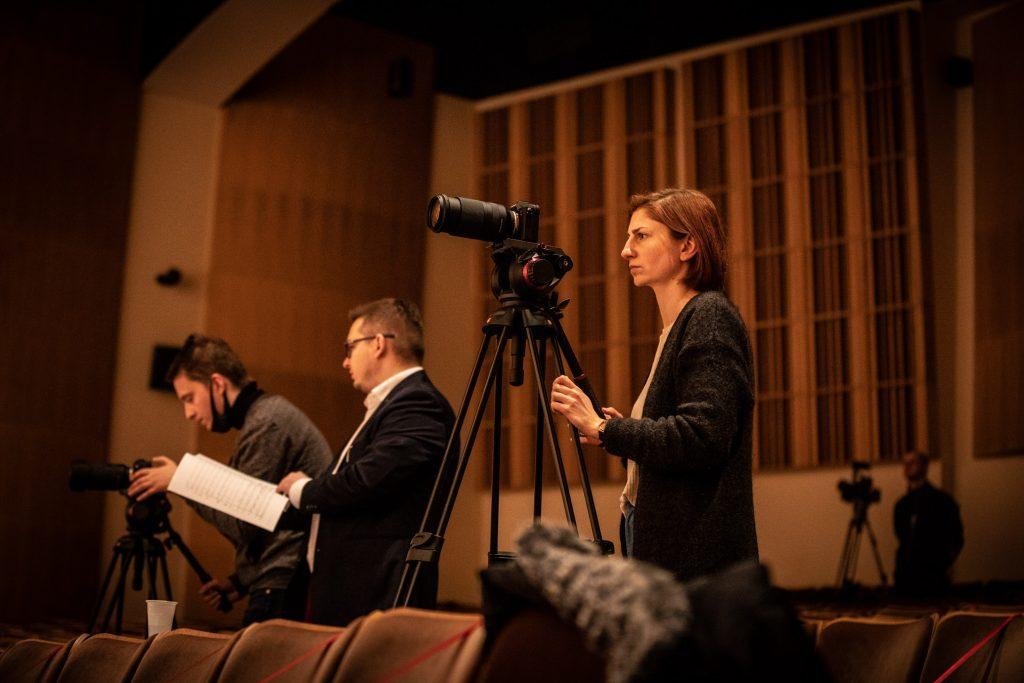 Zbliżenie na kobietę stojącą na widowni przed aparatem. Obok niej stoi dwóch mężczyzn , jeden z nich trzyma nuty, drugi patrzy na aparat stojący przed nim. W oddali widać mężczyznę przy statywie z kamerą.