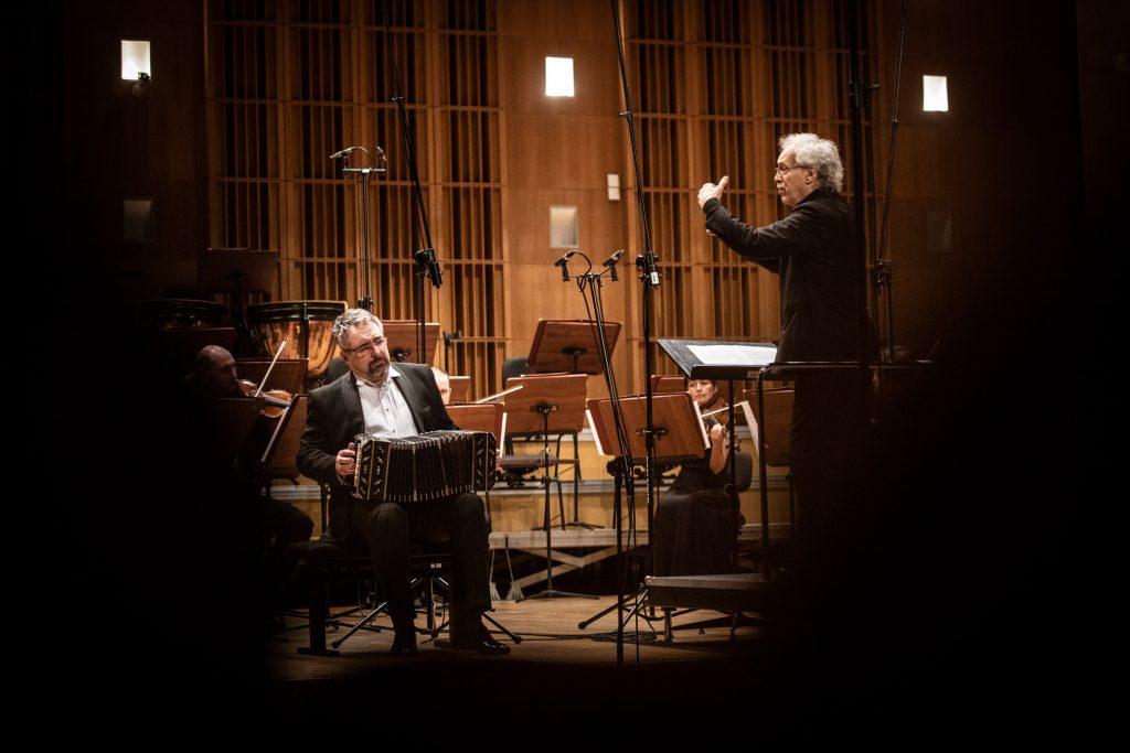 Na podeście po prawej stronie kadru stoi dyrygent. Przed nim siedzi grupa smyczkowa orkiestry. Po lewej stronie mężczyzna gra na bandoneonie.