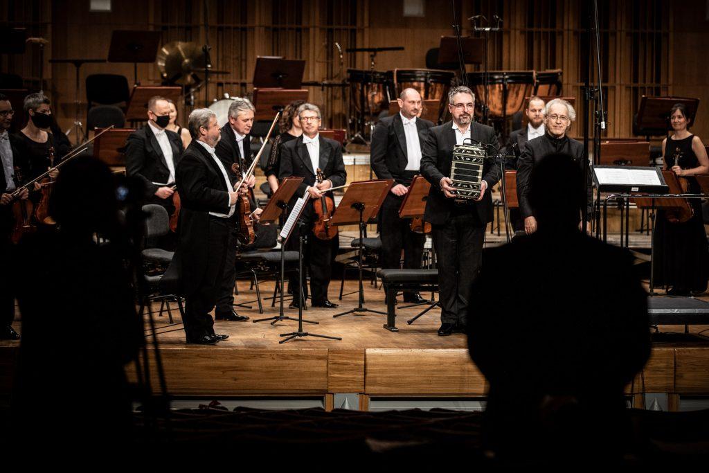 Przy pulpitach na scenie stoi grupa smyczkowa orkiestry. Pośród nich stoi dyrygent oraz mężczyzna trzymający bandoneon.